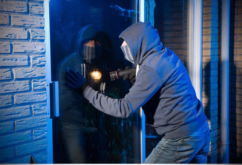 image of a burglar attempting to break a glass